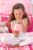 Smiling girl saving money in a piggy-bank Royalty Free Stock Photos