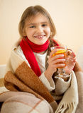 Smiling girl in scarf covered in plaid holding cup of hot tea Stock Image