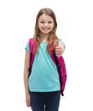 Smiling girl with school bag showing thumbs up. Education, gesture and school concept - happy and smiling little girl with school bag showing thumbs up Royalty Free Stock Photo