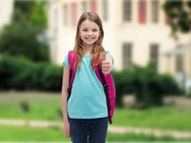 Smiling girl with school bag showing thumbs up Royalty Free Stock Photography