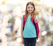 Smiling girl with school bag showing thumbs up Stock Photography