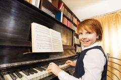 Smiling girl in school uniform playing the piano Stock Image
