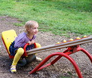 Smiling girl on seesaw Stock Image