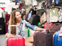 Smiling girl selecting suitcase Royalty Free Stock Images