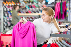 Smiling girl selecting a warm jacket in the sport boutique. Smiling girl selecting a warm jacket at the sport boutique Royalty Free Stock Photo