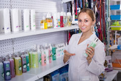 Smiling girl seller advising on pet shampoo. In pet shop Stock Photos