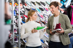 Smiling girl seller helping a customer in shoes department Stock Image