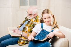 Smiling girl and senior man sitting on sofa and reading books. Adorable smiling girl and senior men sitting on sofa and reading books Stock Image
