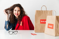 Smiling girl shopaholic sitting with paper shopping bags Royalty Free Stock Photography