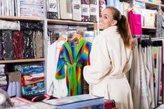 Smiling girl shopper examining new bathrobe Stock Image