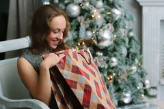 Smiling girl with shopping bags near the christmas tree - christmas and new year concept stock photos