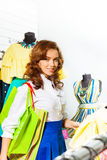 Smiling girl with shopping bags in showroom Royalty Free Stock Photography