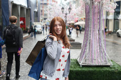 Smiling girl with shopping bags. Street as background Stock Images