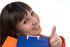Smiling girl at shopping with colourful bags shows good sign Royalty Free Stock Photography
