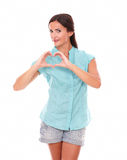Smiling girl in short jeans making a love sign Stock Photos