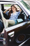 Smiling girl in short shorts in open car, tinted photo Royalty Free Stock Photography