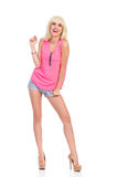 Smiling girl in shorts and high heels. Smiling blond fashion girl posing in high heels and pink top. Full length studio shot isolated on white Stock Images