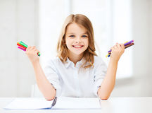 Smiling girl showing colorful felt-tip pens Royalty Free Stock Image
