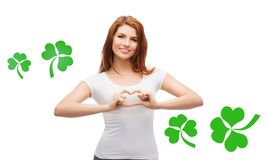 Smiling girl showing heart gesture with shamrock Royalty Free Stock Photos