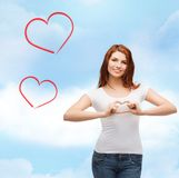 Smiling girl showing heart with hands Royalty Free Stock Photo