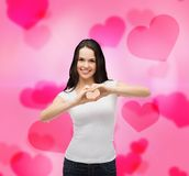 Smiling girl showing heart with hands Stock Photography