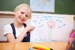 Smiling girl showing her drawing. In a classroom Royalty Free Stock Images