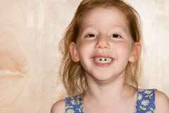 Smiling girl showing her fallen off snaggle teeth Royalty Free Stock Image