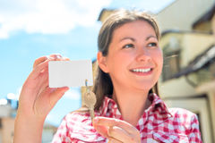 Smiling girl showing the key of the townhouse Royalty Free Stock Photos