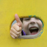 Smiling girl showing ok out of the window at the Stock Photo