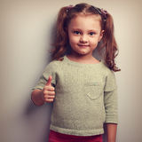 Smiling girl showing thumb up sign and looking happy. Vintage po Royalty Free Stock Photo