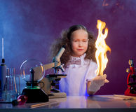 Smiling girl shows chemical trick - fire in palm Stock Images