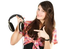 A smiling girl shows a finger on headsets Royalty Free Stock Photo