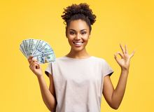 Smiling girl shows money cash and excellent sign, demonstrates that everything is fine. Photo of african american girl wears casual outfit on yellow background royalty free stock image