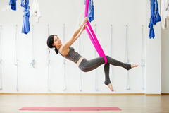 Smiling girl in silk hammock building strength and flexibility of her body. Aerial yoga exercise or antigravity yoga indoors, woman meditating in sport studio Royalty Free Stock Images