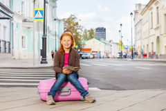 Smiling girl sit on pink luggage with city map Royalty Free Stock Photos