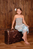 Smiling girl sits on the ancient brown scratched suitcase Stock Photos