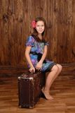 Smiling girl sits on the ancient brown scratched suitcase Royalty Free Stock Images