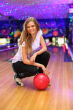 Smiling girl sits with ball in bowling club Royalty Free Stock Images