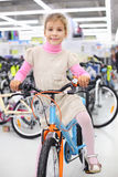 Smiling girl sits on bicycle and looks at camera Stock Photo