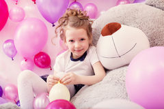 Smiling girl sits leaning on big teddy bear Royalty Free Stock Images