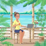 Smiling Girl  Sits at Tropical Coast. Pretty smiling girl in glasses sits on terrace near tropical sea beach. Young woman drinks juice and works on laptop Stock Photos