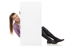 Smiling Girl Sitting Behind White Placard Royalty Free Stock Photography