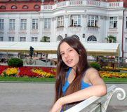 Smiling girl sitting on a bench Stock Photo