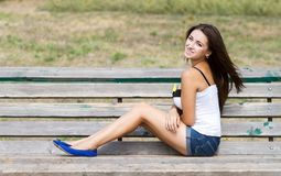 Smiling girl sitting on a bench Royalty Free Stock Image