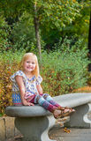 Smiling girl sitting on bench in city park Stock Images