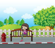 A smiling girl sitting on a bench Royalty Free Stock Photos