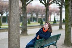 Smiling girl sitting on a bench in park Royalty Free Stock Image