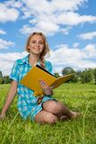 Smiling girl sitting with book Stock Photography