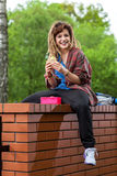 Smiling girl sitting on brick wall and eating lunch Stock Photography