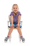 Smiling girl sitting on a chair Royalty Free Stock Image